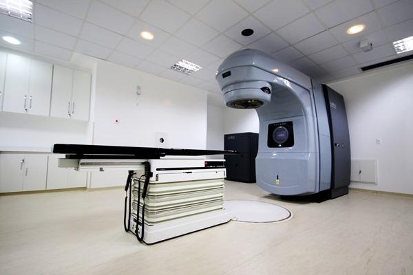 Aparelho de radioterapia. Consiste de uma mesa de exames e o aparelho que remete a um poste de luz