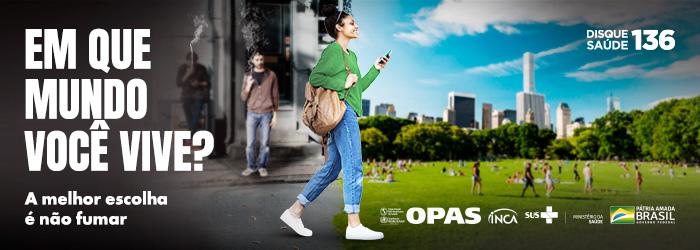 Em que mundo você vive? A melhor escolha é não fumar. Disque saúde 136. [Mulher vestindo um suéter verde, jeans e tênis branco, tem uma bolsa a tiracolo e segura cum celular. Ela caminha descontraída, saindo de um ambiente urbano e poluído em direção a um grande parque arborizado.