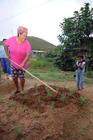 Senhora cava um chão de terra com plantações. Do lado direito dela, uma criança pequena com uma máquina de fotografar em mãos