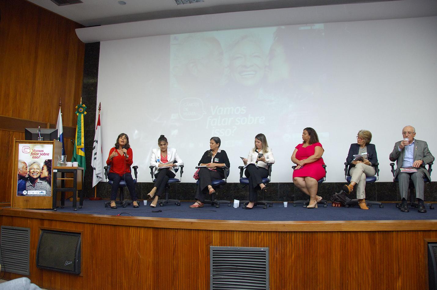 Seis mulheres e um homem sentados em cadeiras em cima de um palco com carpete azul, enquanto uma delas fala ao microfone. Atrás está sendo projetada a imagem da campanha com um senhor e uma jovem beijando no rosto uma senhora, todos negros