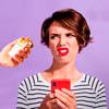 Mulher reage com cara de repulsa aos cigarros oferecidos a ela. A mulher segura um celular vermelho e veste uma camisa com listras brancas e pretas em um fundo lilás.
