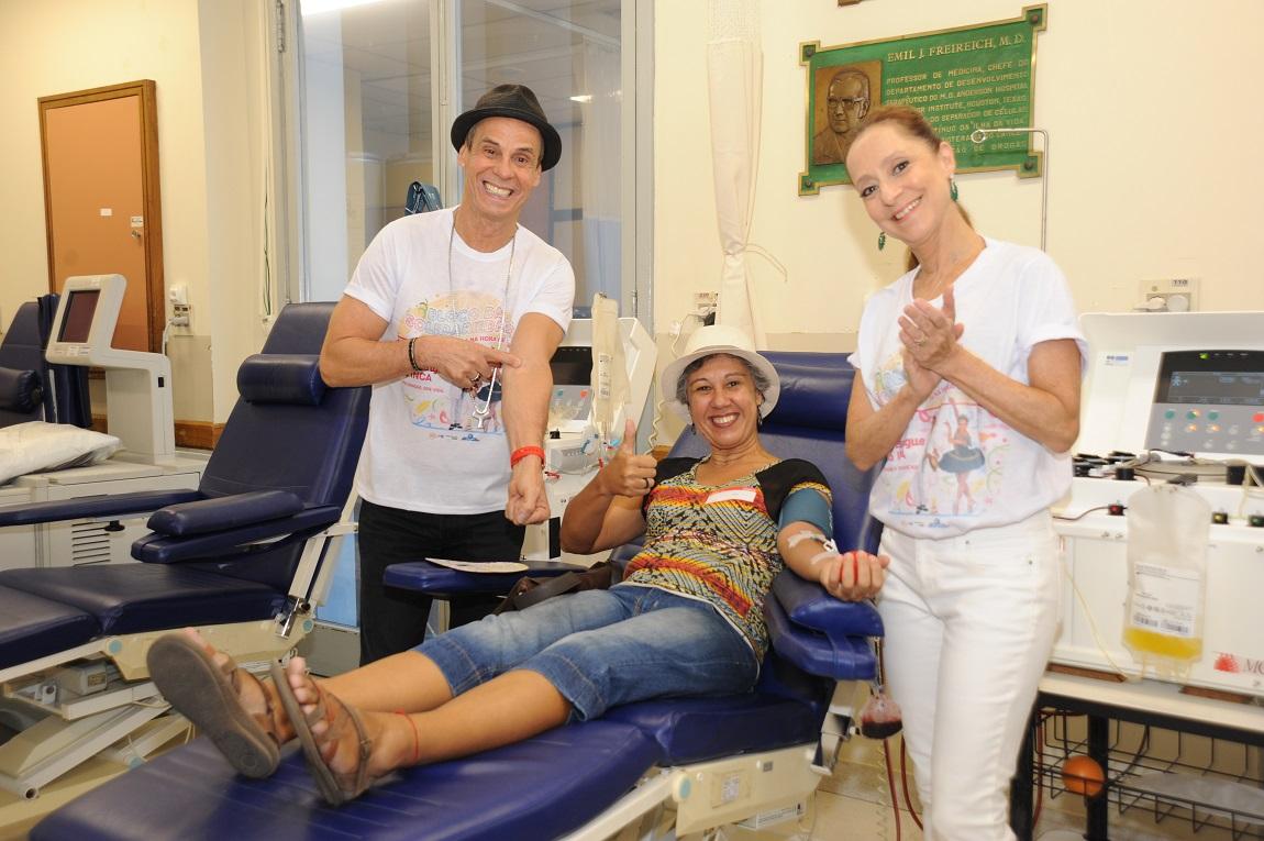 Carlinhos de Jesus em pé, do lado de uma doadora sentada na cadeira de coleta, e Ana Botafogo