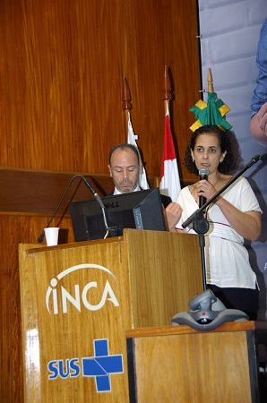 Os pesquisadores André Pichon e Marcia Pinto em cima do palco, atrás de um púlpito