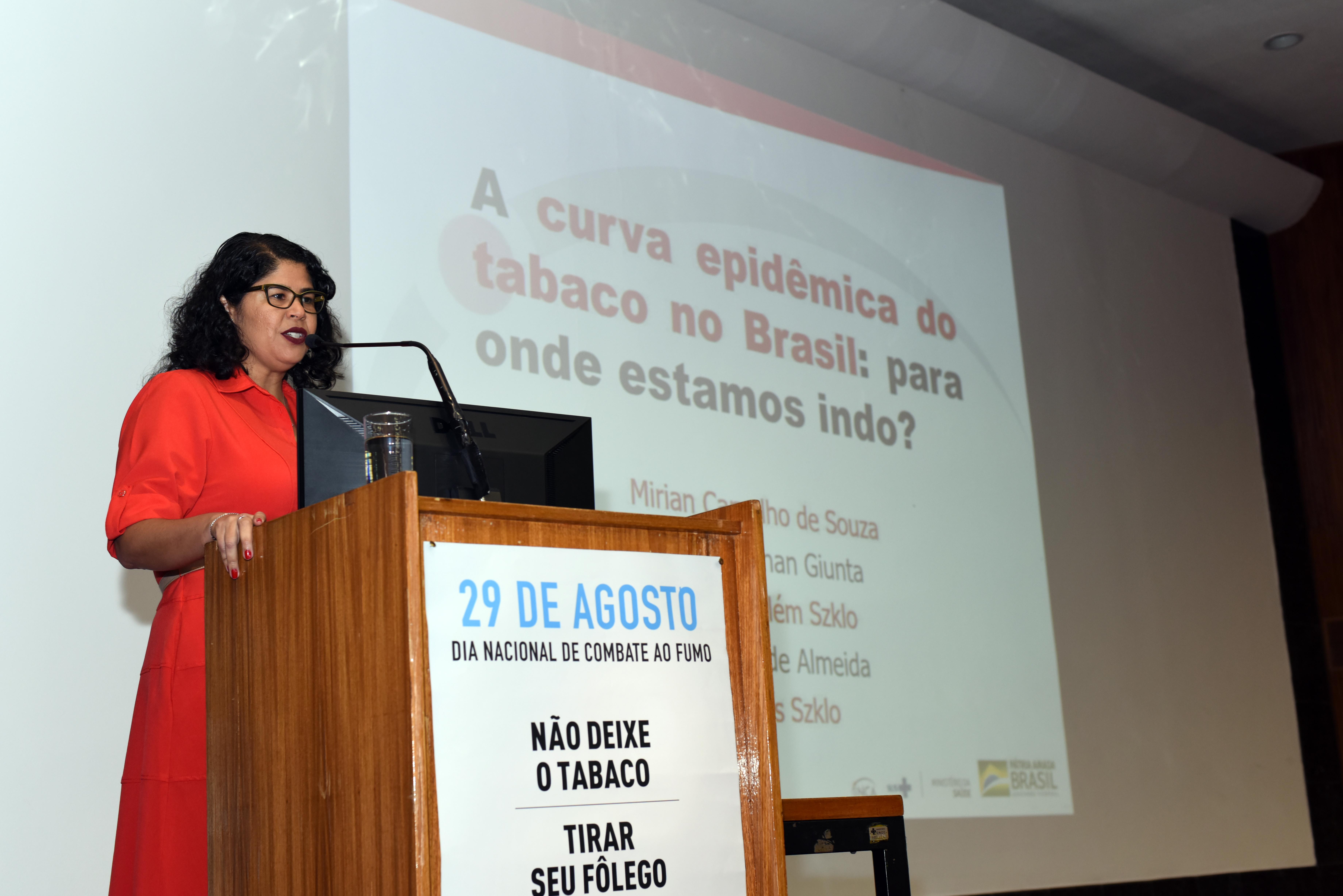 Pesquisadora Mirian Carvalho, da Divisão de Pesquisa Populacional do INCA, no palco, apresentando as conclusões do estudo sobre mortalidade no Brasil por câncer de pulmão