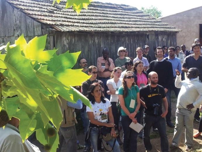 Diversas pessoas em pé em frente a uma casa de madeira