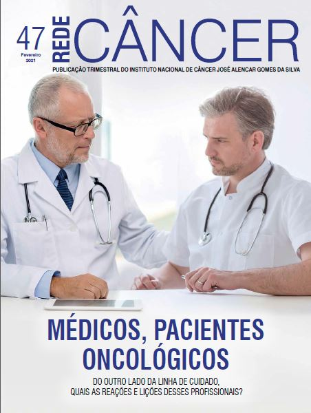 dois médicos sentados atrás de uma mesa, sendo que um dos dois está na posição de paciente