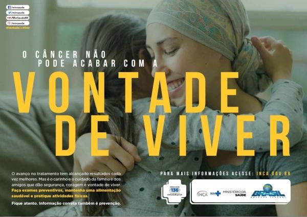 Mulher com câncer sorri enquanto abraça a filha. O cartaz informa que o câncer não pode acabar com a vontade de viver.