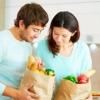 Casal segurando pacotes de compras, com alimentos saudáveis como frutas, legumes e hortaliças