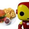 Ao fundo, um prato com lanche, batatas fritas sorridentes e um pote de molho tipo catchup. Na frete um brinquedo de super-heroi.