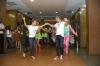 Ana Botafogo segura a mão de Carlinhos de Jesus. Ambos estão dançando no meio do corredor do Hospital, e ao fundo, pessoas dançam e tocam bateria.