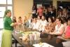 Uma mulher atrás de uma mesa vestindo roupa de chefe de cozinha está falando para uma plateia sentada à frente dela. Em cima da mesa existem objetos de cozinha, como travessas de vidro, raladores, saleiros e alguns alimentos como verduras e legumes.
