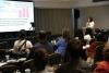 Uma plateia está assistindo uma mulher que usa roupas brancas, cabelo preto e óculos com um controle na mão falar ao microfone à frente deles. Em frente também existe um telão com um slide projetado com gráficos estatísticos.